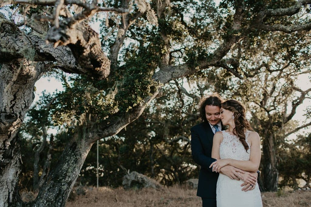 Wedding couple standing under our amazing oak tree backdrop.